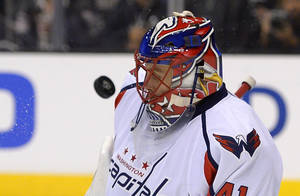 Photo - Washington Capitals goalie Jaroslav Halak, of Slovakia, deflects a shot off his mask during the second period of an NHL hockey game against the Los Angeles Kings, Thursday, March 20, 2014, in Los Angeles. (AP Photo/Mark J. Terrill)