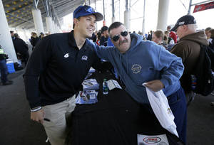 Photo - Trevor Bayne poses for a photo with Bob Johnson, of Sioux City, Iowa, right, during an autograph session before the NASCAR Nationwide auto race, Sunday, May 18, 2014, at Iowa Speedway in Newton, Iowa. (AP Photo/Charlie Neibergall)
