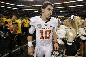 Photo - Oklahoma State quarterback Clint Chelf (10) leaves the field after the Cotton Bowl NCAA college football game against Missouri, Friday, Jan. 3, 2014, in Arlington, Texas. Missouri won 41-31. (AP Photo/Brandon Wade)