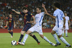 photo -   FC Barcelona's Lionel Messi from Argentina, left, vies for the ball with Granada's Juanma Ortiz, center, during a Spanish La Liga soccer match at the Camp Nou stadium in Barcelona, Spain, Saturday, Sept. 22, 2012. (AP Photo/Manu Fernandez)
