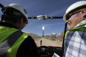 Photo -  Jeff Holland, right, talks with Noel Hanson on Tuesday near a solar power system in Primm, Nev. The Ivanpah Solar Electric Generating System, sprawling across roughly 5 square miles of federal land near the California-Nevada border, will be opened formally Thursday after years of regulatory and legal tangles. AP Photo  <strong>Chris Carlson -  AP </strong>