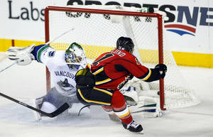Photo - Vancouver Canucks goalie Eddie Lack, from Sweden, left, lets in a goal by Calgary Flames' Mikael Backlund, from Sweden, during second period NHL hockey action in Calgary, Alberta, Sunday, Oct. 6, 2013. (AP Photo/The Canadian Press, Jeff McIntosh)