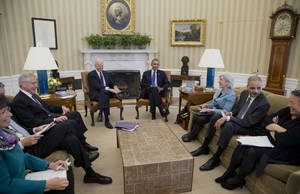 Photo - President Barack Obama and Vice President Joe Biden, center, meet with, from left, White House Senior Adviser Valerie Jarrett, Education Secretary Arne Duncan, Defense Secretary Chuck Hagel, Health and Human Services Secretary Kathleen Sebelius, Attorney General Eric Holder, and Executive Director of the White House Council on Women and Girls, Tina Tchen, who is also the Director of the White House Office of Public Engagement, in the Oval Office of the White House in Washington, Wednesday, Jan. 22, 2014, to discuss the Council on Women and Girls.  (AP Photo/Carolyn Kaster)