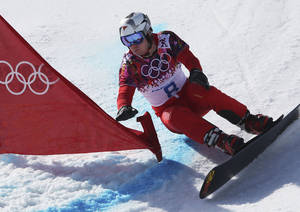 Photo - Switzerland's Nevin Galmarini competes during men's snowboard parallel giant slalom heats at the Rosa Khutor Extreme Park, at the 2014 Winter Olympics, Wednesday, Feb. 19, 2014, in Krasnaya Polyana, Russia. (AP Photo/Sergei Grits)