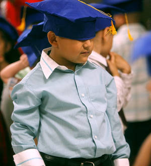 Photo -  Lance Vasquez covers his eyes with his graduation cap Tuesday before the start of a pre-K graduation for Heronville Elementary. Photos by KT King/The Oklahoman  <strong>KT King -   </strong>