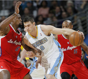 Photo - Denver Nuggets forward Danilo Gallinari, right, of Italy, works the ball inside against Los Angeles Clippers center DeAndre Jordan in the first quarter of  an NBA basketball game in Denver, Thursday, March 7, 2013. (AP Photo/David Zalubowski)