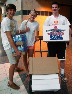Photo - Edmond Santa Fe High School Student Council members, from left, Storm Rund, Julie Stockton and Kaleb Kadavy help move boxes of food and water they collected for tornado victims. PHOTO PROVIDED BY EARL KIRKPATRICK, NEWSOK.COM CONTRIBUTOR  <strong></strong>