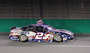 Photo - Brad Keselowski takes a victory lap the wrong way in front of the grandstand after winning the NASCAR Sprint Cup series auto race Saturday, June 28, 2014 at Kentucky Speedway in Sparta, Ky. (AP Photo/Garry Jones)