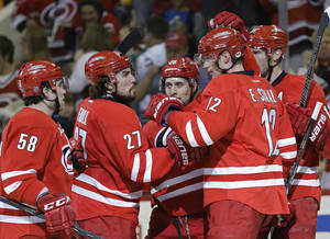 Photo - Carolina Hurricanes' Chris Terry (58), Justin Faulk (27), John-Michael Liles (26), Eric Staal (12) and Jordan Staal, back right, celebrate Liles' goal against the Dallas Stars during the second period of an NHL hockey game in Raleigh, N.C., Thursday, April 3, 2014. (AP Photo/Gerry Broome)