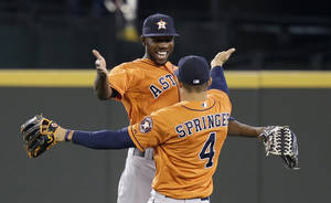 Photo - Houston Astros' Dexter Fowler, left, and George Springer (4) share congratulations after the team beat the Seattle Mariners in a baseball game Sunday, May 25, 2014, in Seattle. The Astros won 4-1. (AP Photo/Elaine Thompson)