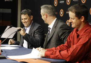 Photo - Former Houston Astros players Lance Berkman, left, and Roy Oswalt, right, sign one-day service contracts as club president Reid Ryan looks on during a news conference before a baseball game against the Los Angeles Angels, Saturday, April 5, 2014, in Houston. Berkman and Oswalt signed the contracts so they could retire as Astros. (AP Photo/Pat Sullivan)