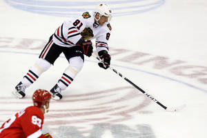 photo - Chicago Blackhawks right wing Marian Hossa (81), of Slovakia, bring the puck up the ice during the third period of their NHL hockey game against the Detroit Red Wings, Sunday, March 3, 2013, in Detroit. The Blackhawks won 2-1 in a shootout. (AP Photo/Duane Burleson)
