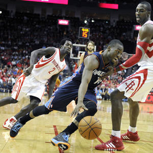 Photo - Charlotte Bobcats' Kemba Walker, center, drives the ball between Houston Rockets Patrick Beverley (2) and Dwight Howard in the first half of an NBA basketball game Wednesday, Oct. 30, 2013, in Houston. (AP Photo/Pat Sullivan)