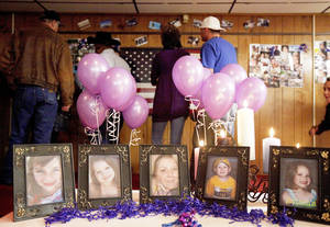 photo - A crowd looks over pictures of Summer Rust and her four children during a vigil in El Reno on Tuesday. All five were slain one year ago in El Reno.  Photo by Bryan Terry, The Oklahoman
