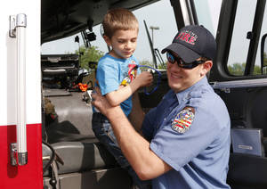 Photo -  Edmond firefighter Chase Olson helps Levi Hagemann, 3, into a fire truck as the YMCA holds Healthy Kids Day at Mitch Park in Edmond. PHOTO BY PAUL HELLSTERN, THE OKLAHOMAN  <strong>PAUL HELLSTERN -   </strong>