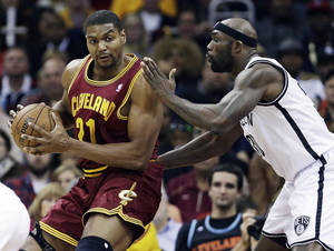Photo - Cleveland Cavaliers' Andrew Bynum, left, tries to get past Brooklyn Nets' Reggie Evans during the first quarter of an NBA basketball game Wednesday, Oct. 30, 2013, in Cleveland. The Cavaliers won 98-94. (AP Photo/Tony Dejak)