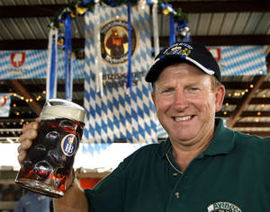 Photo - Mike Turek lifts a stein filled with German beer as he and other workers set up tables and chairs for this year's Oktoberfest at Choctaw Creek Park. The annual event opened Friday and ends at midnight Sept. 8.  Photo by Jim Beckel, The Oklahoman