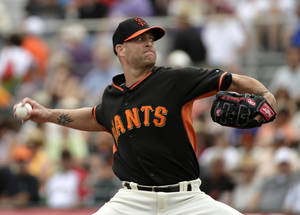 Photo - San Francisco Giants starting pitcher Tim Hudson throws to the Cincinnati Reds during the first inning of a spring training baseball game in Scottsdale, Ariz., Thursday, March 6, 2014. (AP Photo/Chris Carlson)