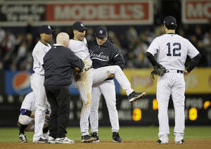 Photo -   Trainer Steve Donohue, second from left, and New York Yankees manager Joe Girardi, second from right, help Derek Jeter off the field after he injured himself during Game 1 of the American League championship series against the Detroit Tigers Sunday, Oct. 14, 2012, in New York. New York Yankees' Robinson Cano, left, and Eric Chavez stood by. (AP Photo/Matt Slocum)