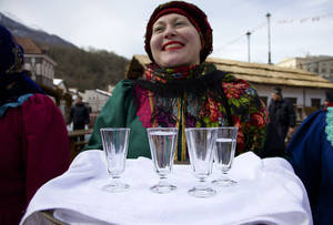 Photo - FILE - In this Feb. 6, 2013, file photo, a woman in a traditional folk costume welcomes guests with a beverage at a street in Rosa Khutor, some 60 km east of the Black Sea resort of Sochi, Russia. Sochi has long been a choice destination for Russia's political elite. Joseph Stalin's summer residence in Zeleni Mys even features a wax mannequin of the dictator at his desk.  (AP Photo/Ivan Sekretarev, file)