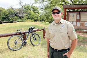 Photo - Roman Nose State Park Manager Travis Lindley talks about the two mountain bikes they use to patrol the trails that were perches with funds eased by Race a Rail, Monday, September 16, 2013.  Photo by David McDaniel, The Oklahoman
