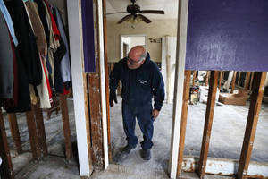 "photo - FILE - In this file photo of Jan. 23, 2013, Anthony Cavallo looks at the doorway to the room of his daughter Amy in Union Beach, N.J., where the family has been living in a trailer next to their home damaged by Superstorm Sandy because the house was uninhabitable as they awaited storm aid. Last week they finally received a check in the mail, marked ""full and final payment,"" for $104,000. Cavallo said that is less than his policy limit, and less than half of what it will cost to rebuild. (AP Photo/Julio Cortez, file)"