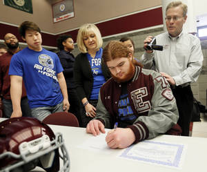 Photo - Jordan Weltzheimer signs to play football with Air Force as his family, from left, brother Jonah Weltzheimer, mother Marie Weltzheimer, sister Jacqlyn Weltzheimer (behind Jordan) and father Ron Weltzheimer, watch during the college signing day ceremony for student athletes at Edmond Memorial High School in Edmond, Okla., Wednesday, Feb. 5, 2014. Photo by Nate Billings, The Oklahoman