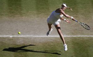 Photo - Eugenie Bouchard of Canada leaps as she plays a rerun to Simona Halep of Romania during their women's singles semifinal match at the All England Lawn Tennis Championships in Wimbledon, London, Thursday, July 3, 2014. Eugenie Bouchard of Canada won the match and will play Petra Kvitova of Czech Republic in the final on Saturday.(AP Photo/Sang Tan, Pool)