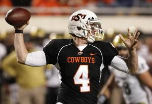 photo - Oklahoma State's Brandon Weeden passes against  Colorado in the third quarter of an NCAA college football game in Stillwater, Okla., Thursday, Nov. 19, 2009. Oklahoma State won the game 31-28. AP Photo