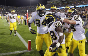 Photo - Michigan running back Fitzgerald Toussaint (28) is congratulated by teammates after his fourth-quarter touchdown against Connecticut in an NCAA college football game, Saturday, Sept. 21, 2013, in East Hartford, Conn. Michigan won 24-21. (AP Photo/Charles Krupa)