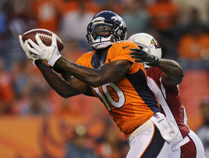 Photo - Denver Broncos wide receiver Gerell Robinson (10) catches a pass as Arizona Cardinals' Javier Arenas defends during the first quarter of a preseason NFL football game, Thursday, Aug. 29, 2013, in Denver. (AP Photo/Jack Dempsey)