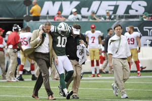 photo -   New York Jets wide receiver Santonio Holmes (10) is helped off the field after being injured during the second half of an NFL football game against the San Francisco 49ers Sunday, Sept. 30, 2012, in East Rutherford, N.J. (AP Photo/Bill Kostroun)