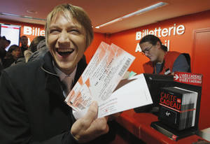 "Photo -   Michael Evanno, 31, shows the tickets he bought for the Rolling Stones concert at Virgin Megastore in Paris, Thursday Oct. 25, 2012. The Rolling Stones announced a surprise ""warm-up gig"" in Paris, and within an hour the Champs Elysees was swarming with fans hoping to get satisfaction with one of the 350 tickets for the Thursday night show. (AP Photo/Francois Mori)"