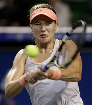 Photo - Eugenie Bouchard of Canada returns the ball against Serbia's Jelena Jankovic during their third round match of the Pan Pacific Open tennis tournament in Tokyo, Wednesday, Sept. 25, 2013. (AP Photo/Shizuo Kambayashi)