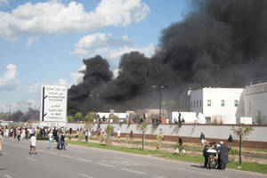 Photo -   A pall of smoke rises above protesters after they set alight cars in the U.S. embassy parking lot in Tunis, Friday, Sept. 14, 2012. some thousands of demonstrators massed outside the embassy and several were seen climbing the outer wall of the embassy grounds, an Associated Press reporter on the scene said. (AP Photo/Amine Landoulsi)