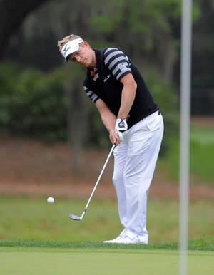 Photo - Luke Donald, of England, chips onto the seventh green during the third round of the RBC Heritage golf tournament in Hilton Head Island, S.C., Saturday, April 19, 2014. (AP Photo/Stephen B. Morton)