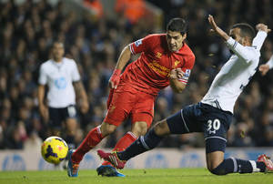 Photo - Liverpool's Luis Suarez, left, shoots and scores the opening goal during their English Premier League soccer match between Tottenham Hotspur and Liverpool at the White Hart Lane stadium in London Sunday, Dec. 15,  2013. (AP Photo/Alastair Grant)