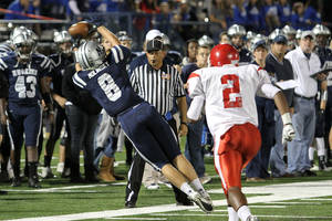 photo - HIGH SCHOOL FOOTBALL: Edmond North's Garrett Molinsky dives to make a catch as Lawton's Maurice Chandler closes in during the Edmond North - Lawton football game Friday night, October 21, 2011, at Wantland Stadium in Edmond. PHOTO BY HUGH SCOTT, FOR THE OKLAHOMAN ORG XMIT: KOD