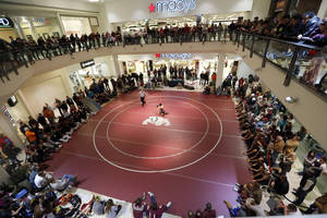 Photo - People watch wrestlers during the high school wrestling dual between Edmond Memorial and Putnam City at Quail Springs Mall in Oklahoma City,  Tuesday,Jan. 15, 2013. Photo by Sarah Phipps, The Oklahoman