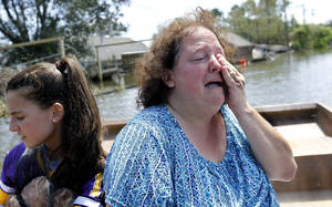 Photo -   Angela Serpas cries as she sees her flooded home for the first time since Hurricane Isaac pushed a 10-foot storm surge into Braithwaite, La., Saturday, Sept. 1, 2012. At right is her daughter Lainy Serpas, 11. While New Orleans streets were bustling again and workers were returning to offshore oil rigs, thousands of evacuees couldn't return home to flooded low-lying areas of Louisiana and more than 400,000 sweltering electricity customers in the state remained without power. (AP Photo/Gerald Herbert)