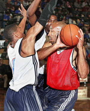 Photo - Michael Ruffin, right, works against Russell Westbrook and Kevin Durant during the Thunder's practice at  Midwest City High School on Oct. 6. Photo by Chris Landsberger, The Oklahoman