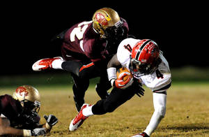 photo - Flowery Branch's C.J. Curry, an Oklahoma State commitment, is tackled by Tucker's Blair Lampkin on Friday, November 25, 2011. PHOTO COURTESY ATLANTA JOURNAL CONSTITUTION <strong>Jonathan Phillips</strong>