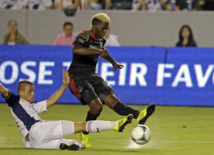 Photo - Real Salt Lake midfielder Luis Gil, left, slides against Los Angeles Galaxy midfielder Gyasi Zardes in the first half of an MLS soccer game in Carson, Calif., Saturday, Aug. 17, 2013. (AP Photo/Reed Saxon)