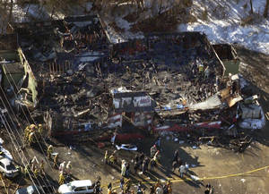 Photo - FILE - In this Feb. 20, 2003 aerial file photo, authorities continue their work at The Station nightclub where more than 100 people died in a late night fire, in West Warwick, R.I. A fire that swept through a crowded nightclub in southern Brazil early Sunday, Jan. 27, 2013, and killed more than 230 people appears to be the deadliest in more a decade. Witnesses said a flare or firework lit by band members may have started the blaze. Similar circumstances led to the the 2003 West Warwick, R.I., fire, where pyrotechnics used as a stage prop by the 1980s rock band Great White set ablaze cheap soundproofing foam on the walls and ceiling of the music venue. (AP Photo/ Robert E. Klein, File)