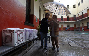 Photo -   Two women share an umbrella as rain falls during the general elections in Mexico City, Sunday, July 1, 2012. (AP Photo/Andres Leighton)