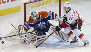 Photo - Calgary Flames' Mikael Backlund (11) is stopped by Edmonton Oilers goalie Ilya Bryzgalov (80) during third period NHL hockey action in Edmonton, Alberta, on Saturday March 1, 2014.  (AP Photo/The Canadian Press, Jason Franson)