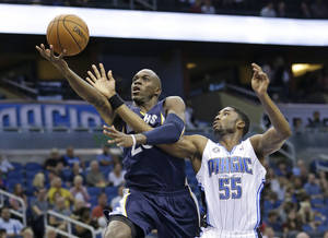 Photo - Memphis Grizzlies' Quincy Pondexter, left, gets to the basket in front of Orlando Magic's E'Twaun Moore (55) during the first half of an NBA preseason basketball game in Orlando, Fla., Friday, Oct. 18, 2013.(AP Photo/John Raoux)