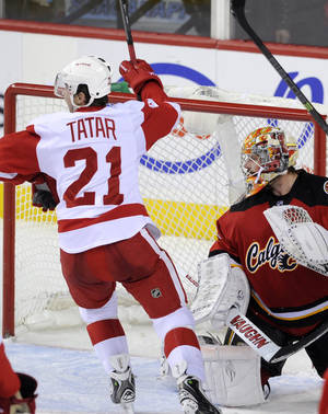 Photo - Detroit Red Wings' Tomas Tartar, left, from Slovakia, celebrates Justin Abdelkader's goal against Calgary Flames goalie Joey MacDonald during the third period of an NHL hockey game in Calgary, Alberta, Friday, Nov. 1, 2013. (AP Photo/The Canadian Press, Larry MacDougal)