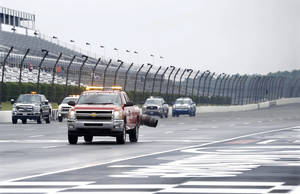 Photo - Trucks use jet engines to dry the track following a rainfall Saturday, Aug. 3, 2013, before practice for Sunday's NASCAR Series auto race in Long Pond, Pa. (AP Photo/Mel Evans)