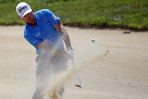 Photo - Graeme McDowell of Northern Ireland chips out of the bunker on the 5th hole, during the first day of the French Open Golf tournament at Paris National course in Guyancourt, west of Paris, France, Thursday, July 3, 2014. (AP Photo/Francois Mori)